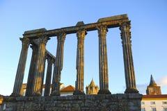 Romersk tempel av Diana och kupolen av domkyrkan på solnedgången, Evora, Portugal arkivbild