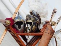 Romerska hjälmar, pilbåge och pilar på de internationella festivaltiderna och epokerna forntida rome Arkivfoto