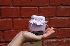 Romig dessert in een kleine glaskruik met decoratie en lint die ter beschikking hielden stock afbeeldingen