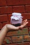 Romig dessert in een kleine glaskruik met decoratie en lint die ter beschikking hielden royalty-vrije stock foto