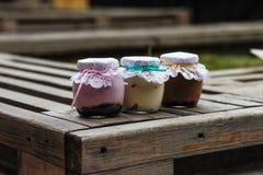 Romig dessert in een kleine glaskruiken met lint op een houten achtergrond royalty-vrije stock fotografie