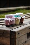 Romig dessert in een kleine glaskruiken met lint op een houten achtergrond stock foto