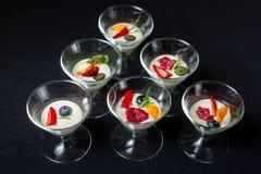 Romig dessert met de zomerbessen in een kom van het glasroomijs stock afbeelding