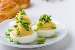 Romig deviled eieren en zoete broodjesbroodjes op feestelijke Pasen-lijst stock foto's