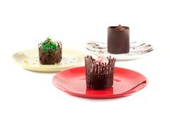 Romige desserts in chocoladeomheiningen Stock Foto
