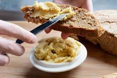 Romige die hummus op geheel tarwe en roggebrood wordt uitgespreid Royalty-vrije Stock Foto's