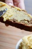 Romige die hummus op geheel tarwe en roggebrood wordt uitgespreid Stock Afbeeldingen