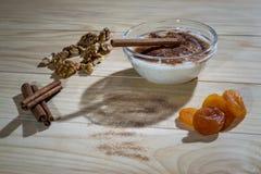 Romige rijstebrij met pijpjes kaneel, okkernoten en droge abrikozen Stock Afbeeldingen