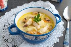 Romige soep met visfilet en mosselen in een blauwe ceramische pot op een witte doek op een grijze abstracte achtergrond Het gezon royalty-vrije stock afbeeldingen