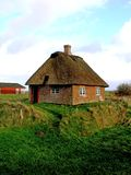 Romo Island Sod Roof Cottage Southern Denmark. Sod roof buildings have been in continuous use in Europe for a thousand years.  This historical cottage on Romo Royalty Free Stock Photo