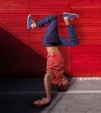 Rompa al bailarín que hace posición del pino contra fondo rojo de la pared Imagen de archivo libre de regalías