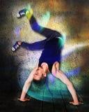 Rompa il ballerino che fa il verticale contro il fondo variopinto della parete Immagini Stock Libere da Diritti