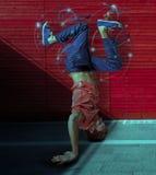 Rompa il ballerino che fa il verticale contro il fondo variopinto della parete Fotografia Stock Libera da Diritti