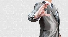 Rompecabezas blanco de la demostración del hombre de negocios a disposición, estrategia empresarial Fotos de archivo