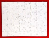 Rompecabezas blanco terminado en fondo rojo Fotos de archivo