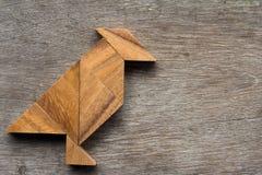 Rompecabezas chino de madera como forma del pájaro en el fondo de madera Foto de archivo