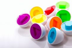 Rompecabezas coloreado educativo plástico de los huevos en un fondo blanco Foto de archivo libre de regalías