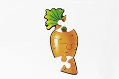 Rompecabezas con la imagen de la zanahoria Fotografía de archivo