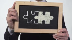 Rompecabezas conectados dibujados en la pizarra en manos del hombre de negocios, símbolo de la sociedad metrajes