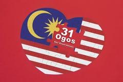 Rompecabezas de la bandera de Malasia de la forma del corazón con una palabra escrita 31 Ogos Foto de archivo