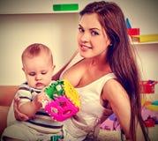 Rompecabezas de la familia que hace la madre y al bebé El rompecabezas del niño desarrolla a niños Imagenes de archivo