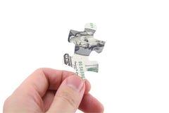 Rompecabezas del dólar del asimiento de la mano imagenes de archivo