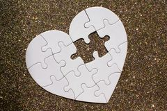 Rompecabezas en forma de corazón blanco en fondo brillante de oro imagenes de archivo