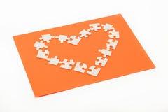 Rompecabezas en la dimensión de una variable de un corazón en una naranja. Foto de archivo libre de regalías
