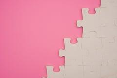 Rompecabezas en un fondo rosado Imágenes de archivo libres de regalías