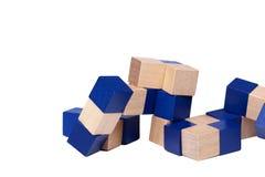 Rompecabezas estimulante de la mente compleja, cubos de madera azules que forman una serpiente aislada en el fondo blanco imagen de archivo libre de regalías