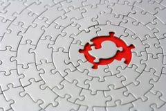 Rompecabezas grises con el espacio y uno de los pedazos que falta en el centro rojo Fotografía de archivo