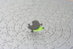 Rompecabezas grises con el pedazo pasado de pie delante del agujero verde Fotografía de archivo