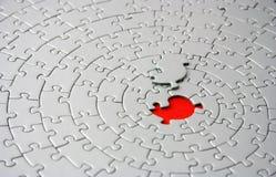 Rompecabezas grises con el pedazo que falta que pone sobre el espacio rojo Fotografía de archivo libre de regalías