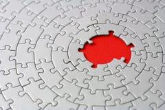 Rompecabezas grises con los pedazos que falta en el centro rojo Fotografía de archivo libre de regalías