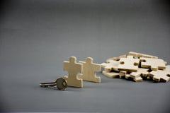 Rompecabezas hecho de la madera con llave en fondo gris con idea del negocio, negocio de MLM o el hombre de negocios Steps al éxi foto de archivo libre de regalías