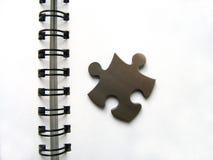 Rompecabezas metálicos en el cuaderno Imágenes de archivo libres de regalías