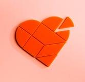 Rompecabezas plástico bajo la forma de corazón con el pedazo disconnected en un fondo rosado Fotos de archivo libres de regalías