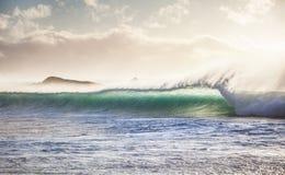 Rompendo l'onda di oceano al tramonto Immagine Stock