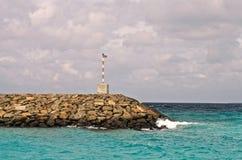 Rompeolas con una pequeña luz en el océano Foto de archivo libre de regalías