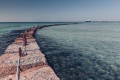 Rompeolas de piedra en el mar Imagenes de archivo