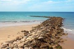 Rompeolas de piedra y playa arenosa Cádiz, España Foto de archivo libre de regalías