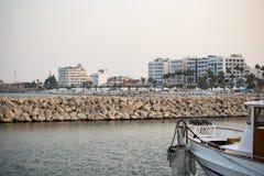 Rompeolas de rocas en Chipre, Larnaca Destino del verano Playa, mar, ciudad, fondo del cielo azul Fotografía de archivo libre de regalías