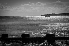 Rompeolas en bahía con el rowing en el mar Foto de archivo libre de regalías