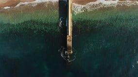 Rompeolas en frente al mar con la opinión aérea horizontal del agua del océano de la turquesa almacen de video