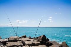 Rompeolas, mar y cielo azul y cañas de pescar Imagen de archivo libre de regalías