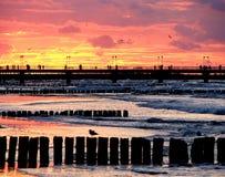 Rompeolas y puesta del sol fotos de archivo