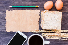 Öron av vete, ägget, gammalt papper och kaffe med skivan av bröd Royaltyfria Foton