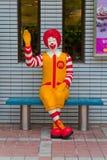 Ronald McDonald, der auf dem Stuhl sitzt lizenzfreies stockbild