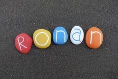 Ronan, nome dado masculino composto com as pedras coloridas sobre a areia vulcânica preta imagem de stock