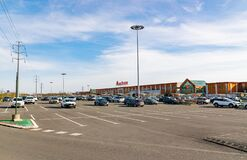 View of Auchan supermarket logo,cars and parking.
